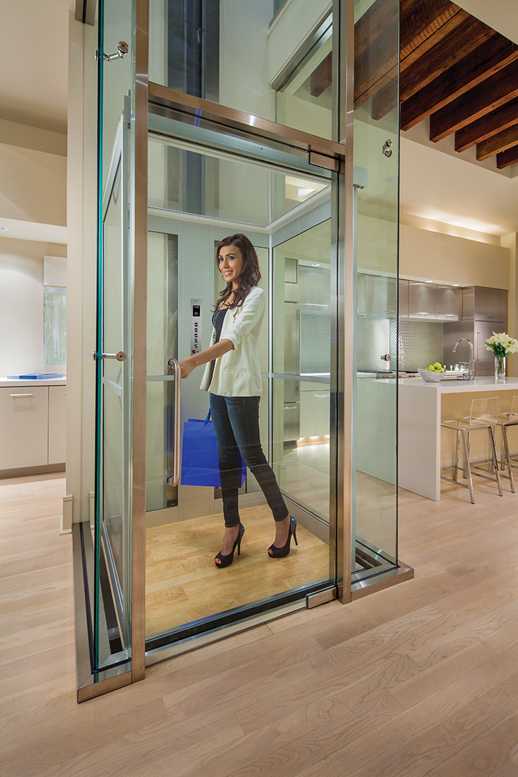 Home elevators prices - Woman In Home Elevator Surrounded By Glass